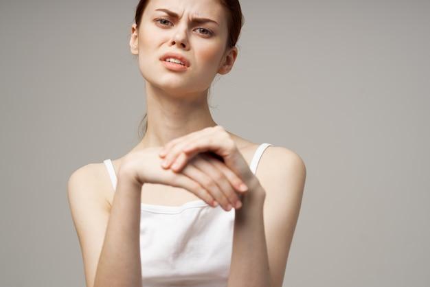 Donna reumatismi dolore al braccio problemi di salute sfondo chiaro