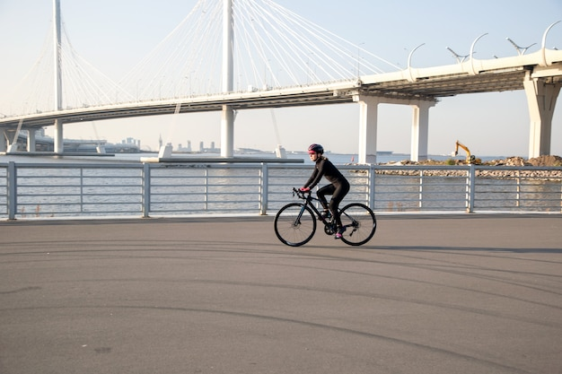 La donna va in bicicletta lungo l'argine sullo sfondo del ponte