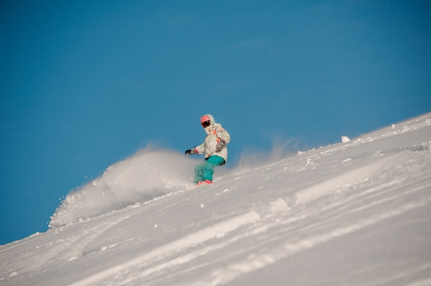 Donna che guida giù per la collina con lo snowboard nella famosa località turistica di gudauri in georgia