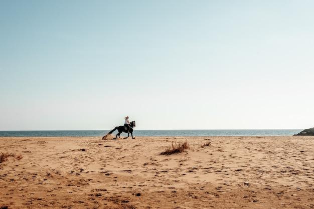 Donna a cavallo in spiaggia