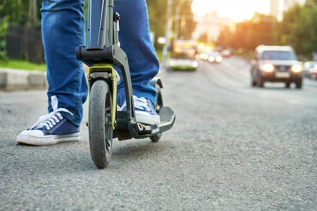 Donna che guida su kick scooter lungo una strada trafficata della città