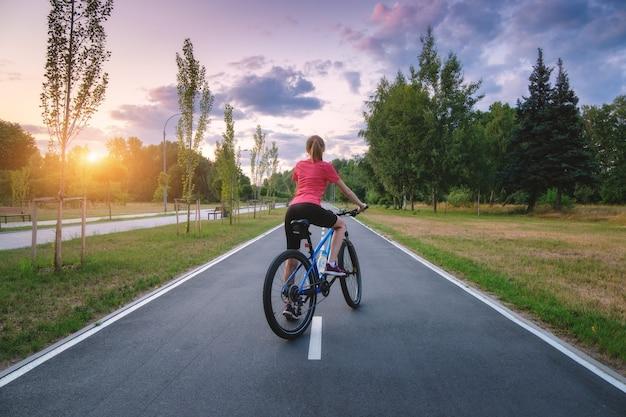 Donna in sella a una mountain bike sulla strada asfaltata al tramonto in estate. paesaggio colorato con ragazza sportiva in sella a una bicicletta, strada, alberi verdi, erba e sunlite d'oro nel parco. sport e viaggi. ciclo