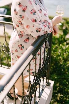 La donna in un abito con un bicchiere di vino in sua mano sta sul primo piano del balcone