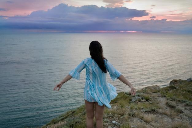 Una donna su una roccia che guarda in lontananza contro il mare