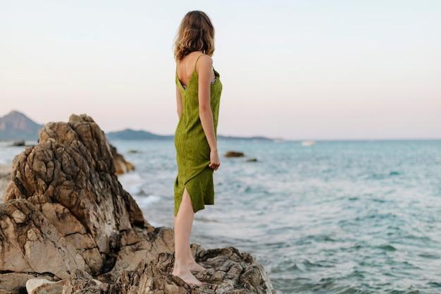 Donna su una spiaggia rocciosa