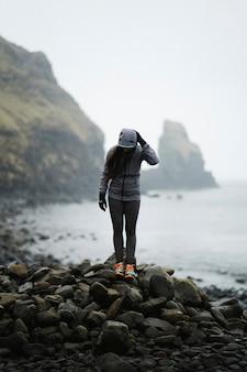 Donna su una spiaggia rocciosa a spar cave, isola di skye Foto Premium