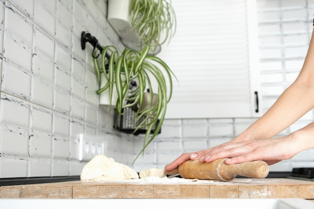 Donna che rotola la pasta sulla tavola di legno con il mattarello di legno