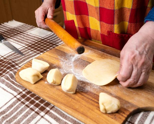 Donna che stende la pasta con un mattarello sul tavolo della cucina.