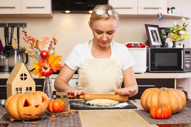 Una donna stende la pasta biscotto per halloween con un mattarello in cucina con un decoro autunnale. fare i biscotti per halloween.