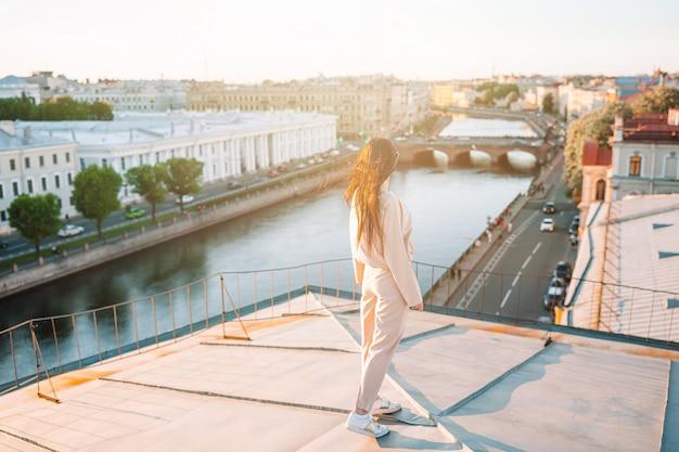 Donna sul tetto che gode con la vista di bello tramonto a san pietroburgo in russia