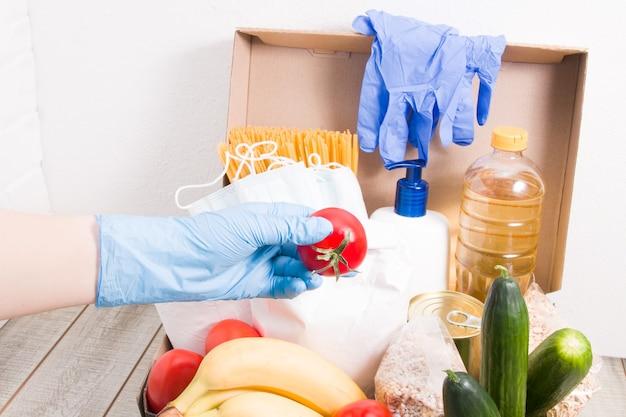 Una donna con un guanto di gomma mette un pomodoro in una scatola con cibo e prodotti per l'igiene per la donazione