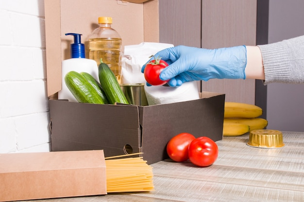 Una donna con un guanto di gomma addolcisce un pomodoro rosso in una scatola con prodotti da donare