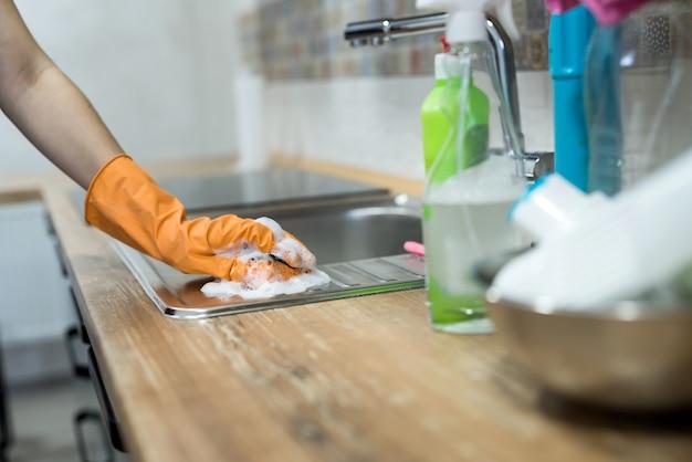 Donna in guanti di gomma che puliscono il lavello della cucina