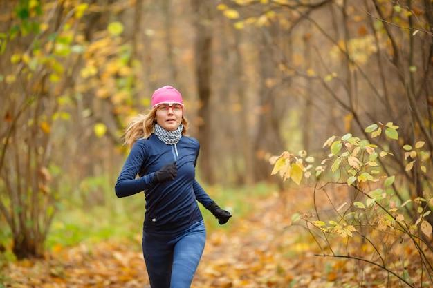 Corridore della donna nella sosta di autunno di mattina. ritratto di belle atlete in movimento