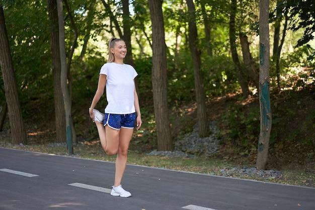Corridore della donna che allunga le gambe prima di esercitare la mattina del parco estivo