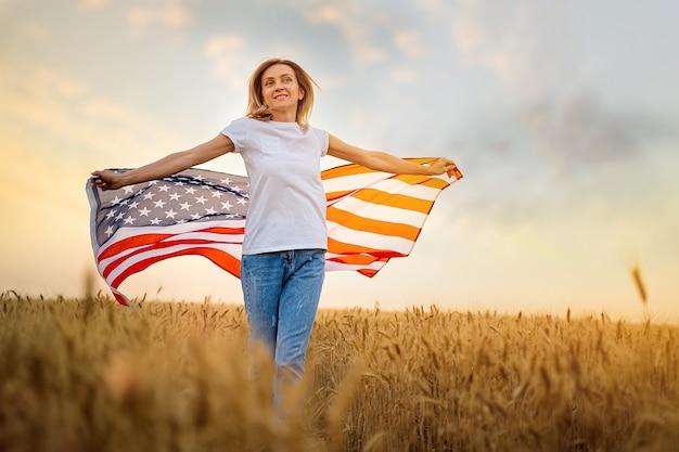 Donna che corre spensierata con le braccia aperte sul campo di grano che tiene una bandiera usa