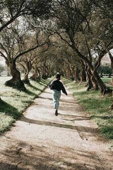 Donna che corre tra alberi giganti in toni vintage durante una giornata di primavera
