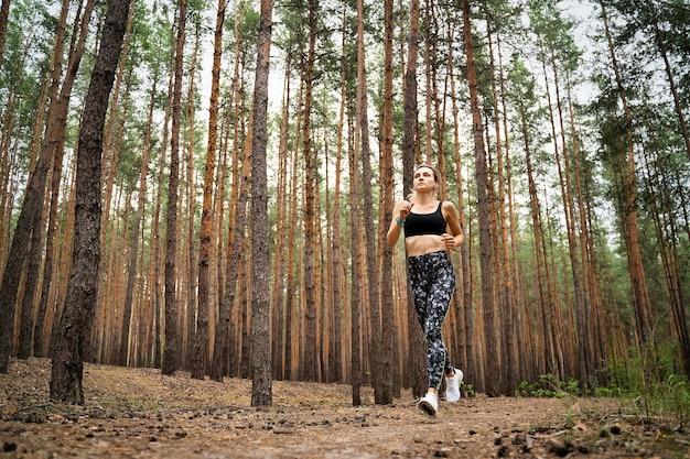 Donna che corre sul sentiero nella bellissima foresta di pini selvatici. concetto di stile di vita attivo.