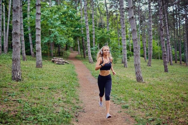 Una donna corre a fare jogging nella foresta.