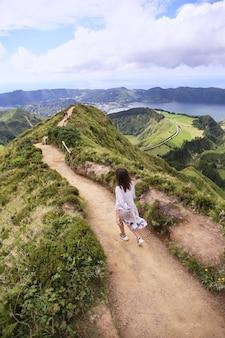 La donna corre attraverso le montagne in un vestito lungo all'aria aperta