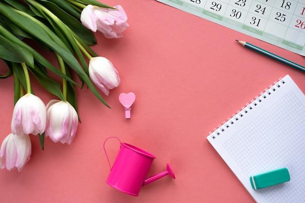Scrivania da donna con calendario, blocco note, annaffiatoio, matita e tulipani.