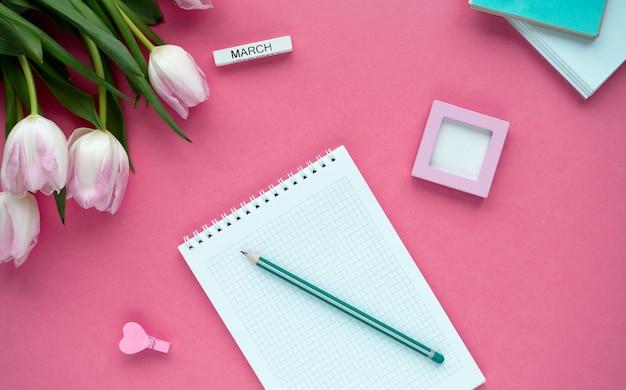 Desktop della donna con blocco note, matita e tulipani