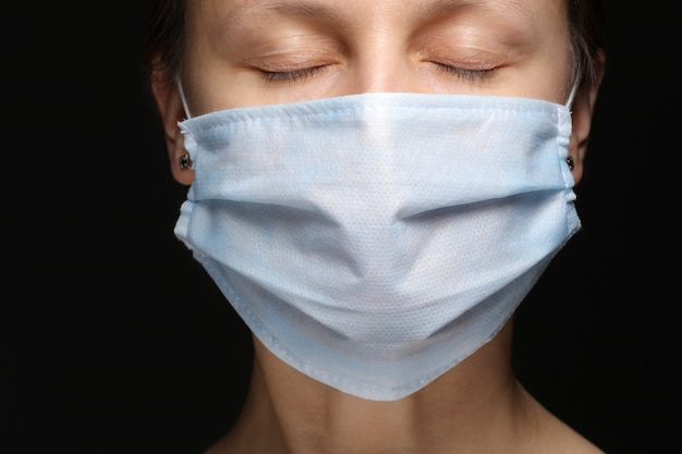 Il volto di una donna in una mascherina medica su fondo nero