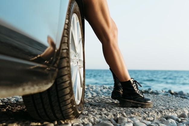 Piedi della donna in piedi in macchina vicino al mare