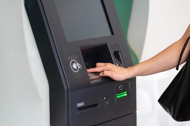 Mano della donna sul bancomat che trasferisce denaro o preleva denaro
