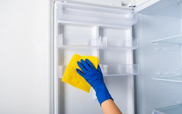 La mano di una donna in un guanto protettivo di gomma blu e uno straccio giallo lava e pulisce i ripiani del frigorifero.