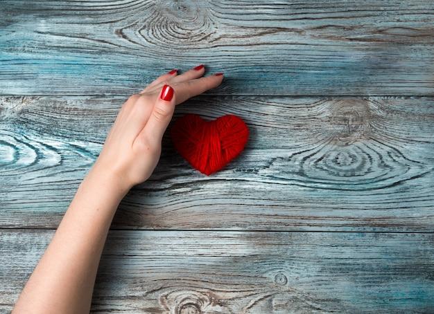 La mano di una donna copre un cuore rosso su uno sfondo di legno. t