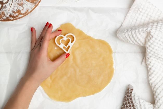 La mano di una donna taglia i biscotti a forma di cuore dalla pasta arrotolata, laici piatta