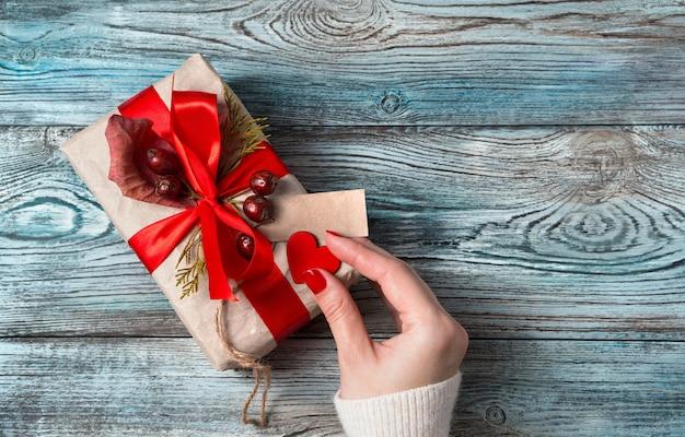 La mano di una donna decora il cuore di una confezione regalo su uno sfondo di legno.