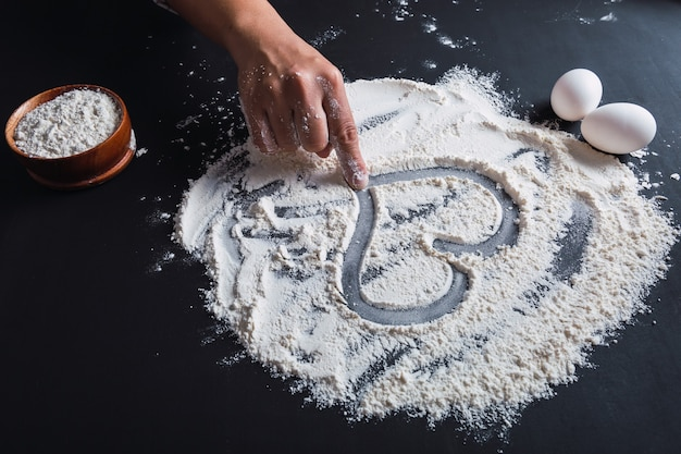 La mano di una donna disegna un cuore sulla farina, cucinando con amore.