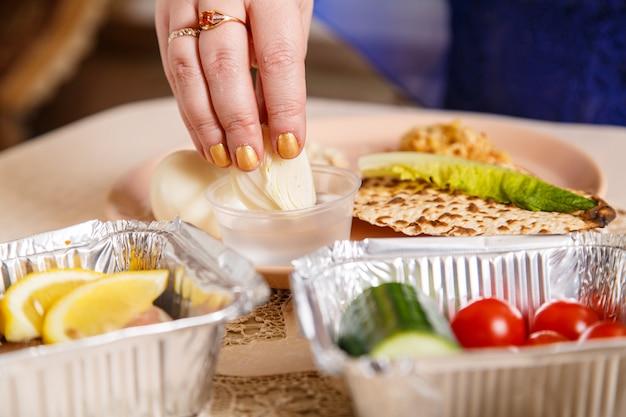 La mano di una donna al tavolo del seder pasquale immerge maror e karpas in acqua salata. foto orizzontale
