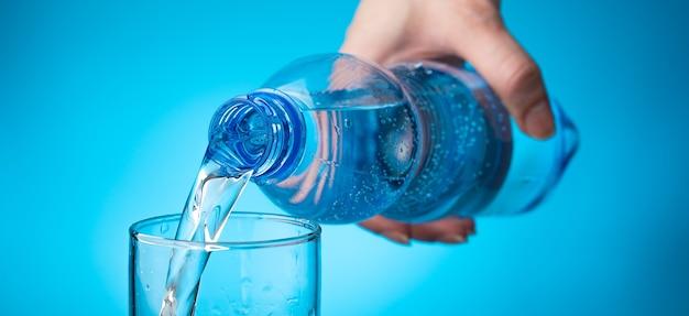 La mano di una donna riempie un bicchiere con l'acqua di una bottiglia su uno sfondo azzurro.