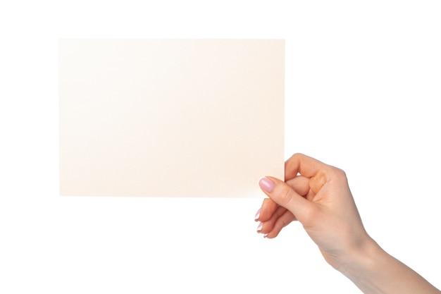 Mano della donna che tiene foglio di carta bianco in bianco isolato su bianco