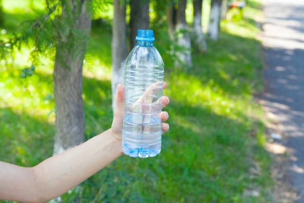 Mano di donna che tiene una bottiglia d'acqua nel parco