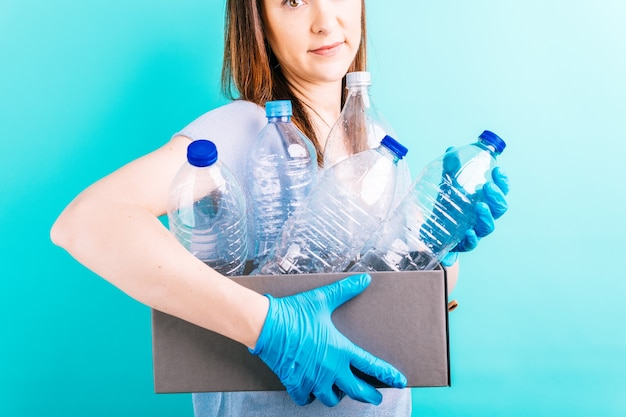 Scatola di contenimento della mano della donna con bottiglie di plastica per il riciclaggio. concetto di riciclaggio. cura dell'ambiente