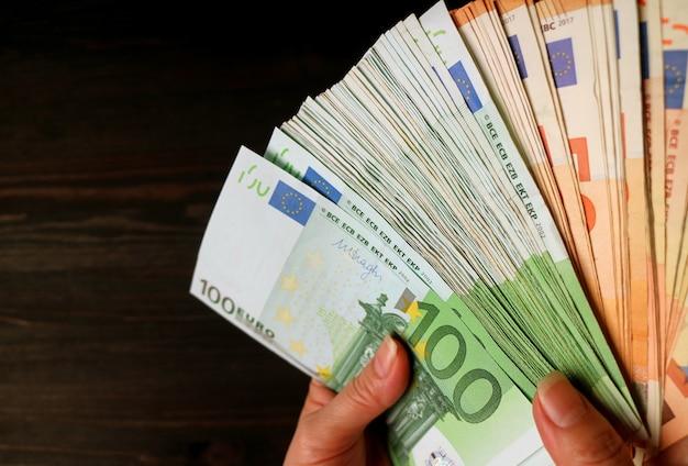 Mano della donna che tiene un mazzo di banconote da 100 e 50 euro