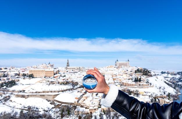 Mano della donna che tiene una sfera di cristallo. vista panoramica innevata della città di toledo in background.