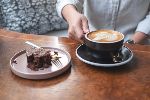 Mano della donna che tiene e beve caffè latte caldo con torta brownie sul tavolo
