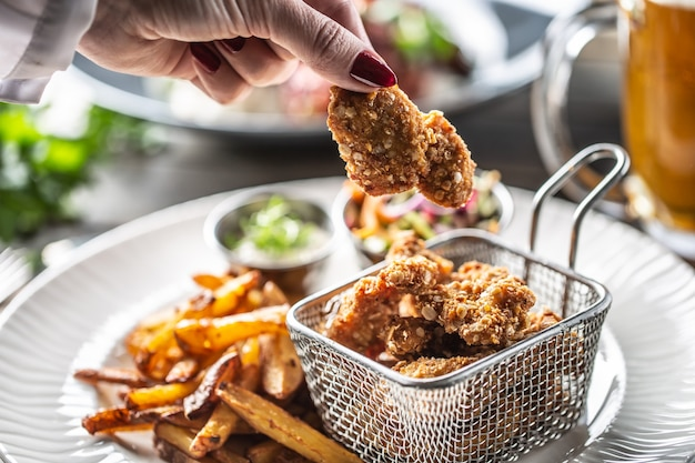Mano della donna che tiene pepita di pollo fritto su un piatto con patatine fritte.