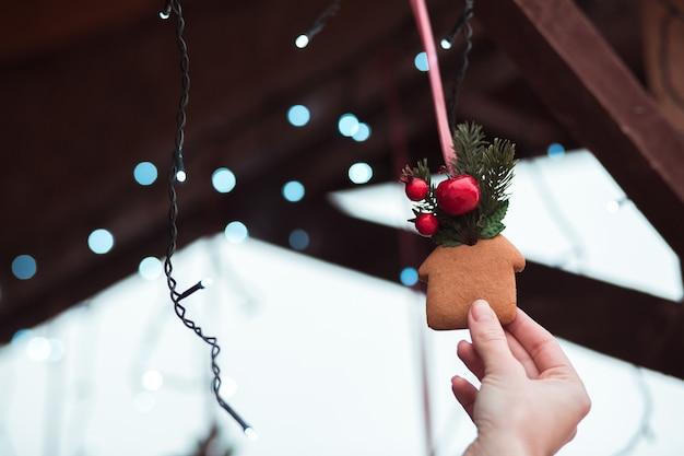La mano della donna che tiene il biscotto di pan di zenzero alla fiera di natale sullo sfondo delle luci