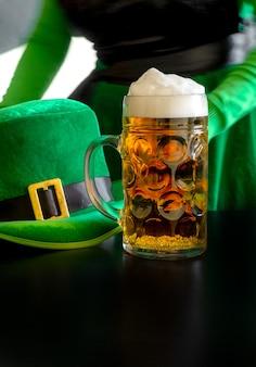 Mano della donna che tiene un bicchiere di birra vicino al cappello di giorno di san patrizio di un leprechaun sul nero