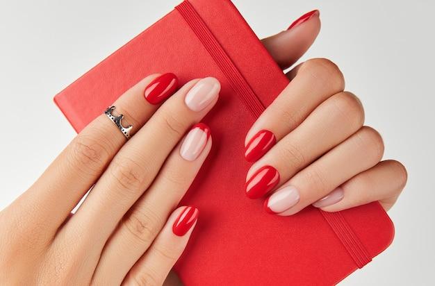 Blocco note della tenuta della mano della donna sopra le tendenze di progettazione del manicure della parete bianca