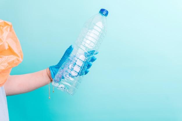 La mano della donna che tiene una bottiglia di plastica per il riciclaggio su sfondo blu. concetto di riciclaggio