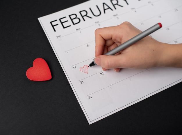 Mano della donna che tiene una penna rossa sopra il 14 febbraio sul calendario cartaceo e cuore di legno rosso su sfondo scuro