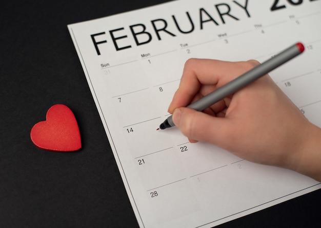 Mano della donna che tiene la penna rossa sopra il 14 febbraio sul calendario di carta e sul cuore di legno rosso