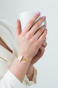 La mano della donna che tiene una tazza di caffè bianca. con un bel primo piano di manicure. bevi, moda, mattina